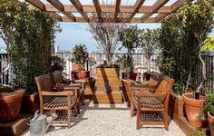 O pergolado, em um canto do terraço, possui paisagismo de Claudia Muñoz. O piso tem área central forrada de pedriscos e entorno do deque de pínus tratado