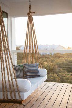 decoracion jardin, veranda con suelo de tarima, sofá blanco colgante con cojines, paisaje con bosque y casas