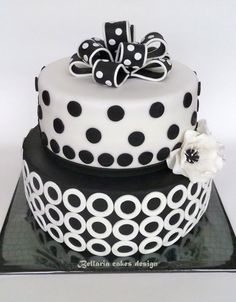 Black and white birthday cake with dots and modern circles. I love the bow on top and the flowers added between the two layers.