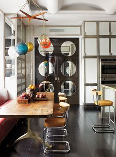 Swinging doors don't always need to be white with small round windows. This fun double door, paired with an eclectic chandelier and diner-style chairs, gives this room a retro yet trendy twist.
