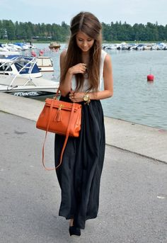 black maxi skirt; great pop of color w/ orange bag; great water background