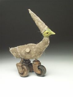 Casey Stueber - Kurtis - ceramic mixed media sculpture with antique caster wheels - surfaced with mud and shredded twine. He wears a tall hat and a button & in his side pocket are his notes for school
