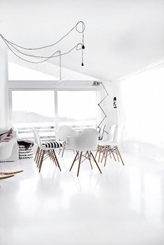 all white living room   Eames chairs   cable pendant lights