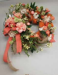 Spring wreath, coral peonies, deco mesh, coral burlap ribbon, green and white vining berries, and hydrangea. Designed by Master Designer Nichole Lefebvre at Silks and Crafts in Denham Springs, LA.