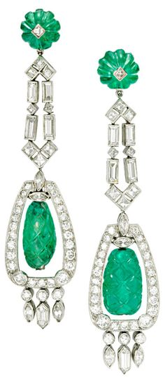 A Pair of Art Deco Emerald and Diamond Ear Pendants, each suspending a carved emerald fluted bead, within a diamond and navette-shaped diamond frame, to the baguette-cut diamond and emerald bead surmount, mounted in platinum, circa 1930. Via 1stdibs.