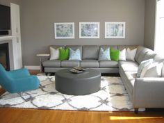 Now this is a family room full of fun! Bright colours, an abundance of pillows, plenty of comfortable seating, a shaggy rug and lots of sunshine. Living Room Grey, Rugs In Living Room, Interior Design Living Room, Living Spaces, Round Ottoman, Bright Colours, Glass Table, Open Shelving, Abundance