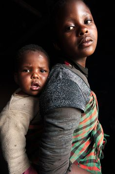 """""""Sunlight hits this young girl's face as she carries her sister on her back, on the way to fetch water."""" Editors' Pick From Our Ongoing Annual Photo Contest: October Photo by Kaitlin Alsofrom. We Are The World, People Around The World, Beautiful Children, Beautiful People, Beautiful Babies, Girl Face, Mother And Child, Photo Contest, First World"""