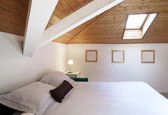 Quarto no sótão com atmosfera intimista. Ambiente confortável com claraboia e iluminação natural.