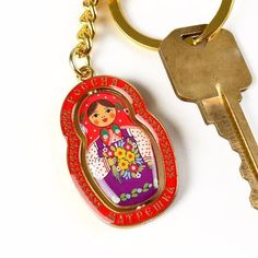 """Russia Matreshka Keychain - $6.99 This fun keychain showcases a brightly colored nesting doll design, that freely turns about inside of a fancy border which says """"Russia"""" at the top and """"Matreshka"""" on the bottom (One side in English, the other in Russian). This matryoshka souvenir came straight to our store from Russia, and it makes a wonderful gift. Colors may vary slightly from the photograph."""