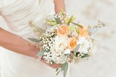A pastel peach and pink wedding bouquet of roses, baby's breath, eucalyptus and peonies {Riverland Studios}