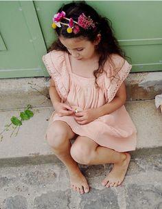 Vestido confeccionado en algodón 100% en color rosa, con detalles de bordados en volantes de los hombros y en la zona de la pechera.