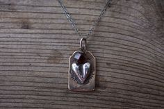 "A rugged sterling heart that could be the size of Texas rests upon a golden tab of bronze.  Embellished with a 4mm faceted garnet.  Hangs from blackened sterling silver chain..75""x.50"" Tab"