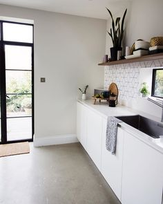 White kitchen with Crittall doors and concrete flooring | minimalistic kitchen design with open shelves | by SHnordic