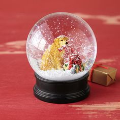 BEST FRIEND SNOWGLOBE  Your best four-legged friend comes bearing gifts—good dog! It's the perfect present and a wonderful way to add to the season's joy. Handpainted.