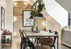 Rustic dining room with green plants, brick wall, light chain and furniture in wood and metal.