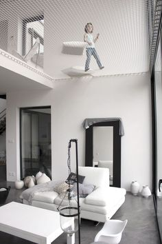 The net above the living room in this modern home creates a play space for kids, and a relaxing spot for grownups.
