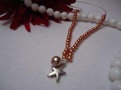 Halskette mit einem Seestern und einer Perle als Anhänger.  Die Kette ist zur einen Hälfte aus einer Gliederkette und zur anderen Hälfte mit kleinen b