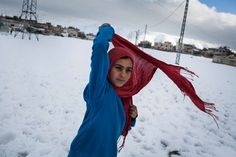 Twelve-year-old Asma'a fixes her headscarf outside her family's shelter in the Bekaa Valley. Winter storm Zina is expected to last a few days and bring temperatures falling well below zero. © UNHCR/A.McConnell