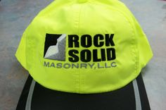 Rock Solid Masonry logo on a safety yellow cap.  Embroidery by Top It Off.