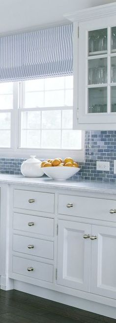 Blue and white beach kitchen with inset cabinets accented with nickel cabinet pulls below a marble counter alongside blue glass brick tiled backsplash with glass upper cabinets framing the sash windows dressed with blue and white striped roman shades.