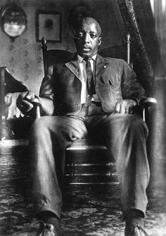 African American man seated in rocking chair in his home. He is wearing a suit with a long, narrow tie. c.1890
