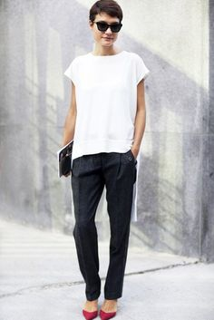 Asymmetric white top, black trousers and red pointed-toe pumps