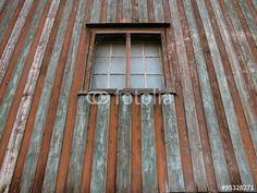 Sprossenfenster in einem alten Stallgebäude mit vergilbter Holzfassade bei Bielefeld in Ostwestfalen