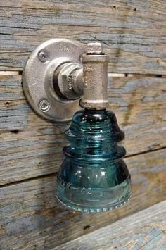 Glass insulator made into wall sconce.