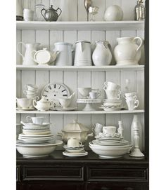 Lovely white dishes on an open shelf.