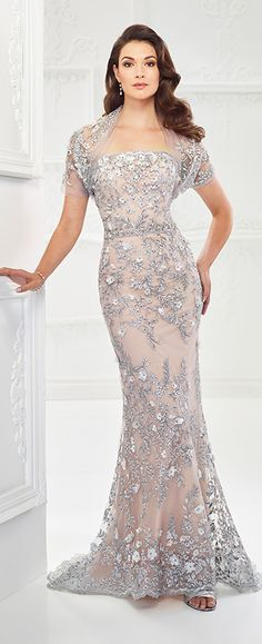 Meticulously detailed, this multiple piece strapless tulle and metallic embroidered lace fit and flare gown is adorned with three-dimensional flowers and heat set stones. It also features a scalloped neckline, a natural waistline that can be accented with a removable beaded waistband or a satin belt, a scalloped lace hem, and a sweep train. A …