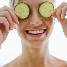 Femme avec des rondelles de concombre sur les yeux