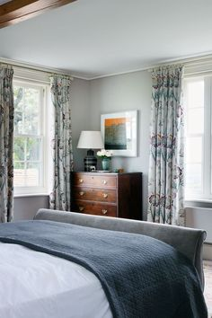 """The main bedroom of [link url=""""http://www.houseandgarden.co.uk/interiors/real-homes/sussex-farm""""]Ptolemy Dean's Sussex newbuild[/link] is decorated in shades of blue and grey. This soothing scheme is finished with touched of dark wood. The curtains are in a floral fabric by [link url=""""https://www.gpjbaker.com/""""]G P & J Baker[/link]. Like this? Then you'll love [link url=""""http://www.houseandgarden.co.uk/interiors/stately-homes""""]Stately Homes[/link]"""