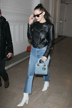 In patched Re/Done jeans, white boots, a baby blue Dior handbag, leather jacket, jeweled choker, silver hoop earrings and Céline sunglasses while out in Paris.