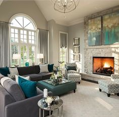 Formal living idea with pop of color: brown couch, revere pewter/stonington grey paint, light gray rug, gray patterned pillows, mirrored accents, silver and white lamps, light gray patterned chairs, pop of color in pillows, artwork, and table decor