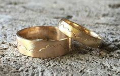 Olympic mountain range wedding bands handmade by the bride and groom. Yellow gold rings.
