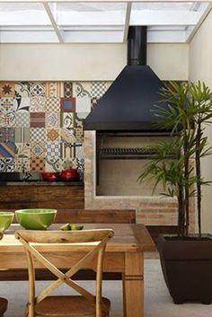 As cores sóbrias desta área externa são complementadas pelos coloridos ladrinhos, que preenchem à parede da churrasqueira.