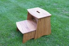 Wood stepstool.  The bottom step slides in & out for storage.  Red oak.