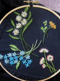 flower embroidery.  Normally flowers are embroidered on a light colored fabric, but the navy blue looks very nice.