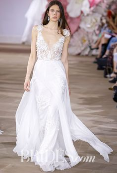 """Brides.com: Ines Di Santo - Spring 2017 """"Chic"""" plunging V-neck wedding dress with re-embroidered appliqués at the bodice and hemline and long sleeve peplum coat with handmade flowers, Ines Di SantoPhoto: Luca Tombolini / Indigitalimages.com"""