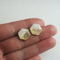 Modern and minimalist these white and gold hexagon studs are the perfect addition to any girls jewelry box. Each stud is handmade from white polymer clay, delicate gold leaf is applied then the earrings are finally coated with a resin which makes them look like glass.  These studs are made from high quality nickle free titanium which is perfect for those with metal sensitivities. The stainless steel comfort clutch backs are nickel free as well and help hold these earrings up straight and…