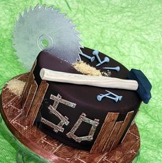 Carpenter cake with saw blade - Thanks for inspiration from other carpenter cakes here on CC.  Saw blade made out of gumpaste, wood, hammer and nails out of modelling fondant.