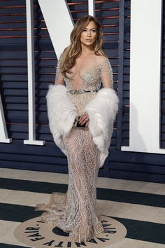 Jennifer Lopez channeled Old Hollywood glamour with a sexy twist at the 2015 Oscar Party wearing a silver and sheer Elie Saab dress with a fur stole. Photo: Helga Esteb / Shutterstock.com