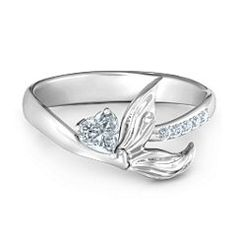 Ariel: You don't need a tail to feel like a mermaid! The band of this beautiful ring features a mermaid tail one one side and five shimmering accent stones on the other. A 4x4mm heart-shaped gemstone compliments the mermaid tail for an added touch of sparkle. Personalize with your choice of metal and engraving.