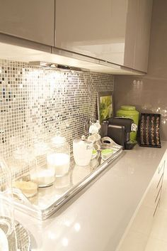 Glossy white counters, white cabinetry with under cabinet lighting, disco inspired glass mirror backsplash and a touch of lime green. Like the backsplash and pop of lime.