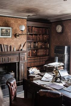 Great space with fireplace, wallpaper, books and old leather chairs...