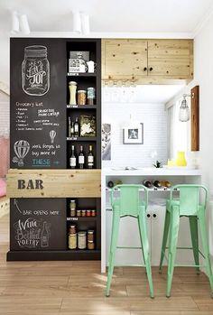 This is an eclectic small bar area with chalkboard cabinetry mixed with unfinished pine and mint green stools. An unforgettable and adorable design idea.