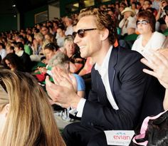 Tom Hiddleston in Wimbledon today...but seriously how in the name of Loki are those women around him focused on a tennis match??? I mean HELLO Hiddles is right there!!! Worship his beautiful self, get him a drink, fan him, or just look at him with drool....do something...but don't watch some stupid ball be hit back and forth on a court with him around....geez!!