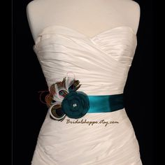 "Teal Peacock Bridal Sash Belt, Bridal Accessories Stunning teal/peacock bridal sash with teal chiffon flower finished with a cluster of seed beads in the center. A dramatic spray of peacock feathers, pink wisps, and ivory feathers accents the side. Message me for custom colors and designs.  This listing is for 1.5"" width double sided satin 3 yards in length   *Each sash is handmade by the Bridalshoppe. There are no two sashes exactly alike adding to their charm.    {©BridalShoppe - all…"