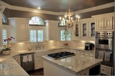 kitchen with white cabinets, white and light gray granite counters, chandelier, gray walls, farmhouse sink, stainless appliances @ Do it Yourself Home Ideas