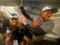 Description of . San Francisco Giants' Hunter Pence pours champagne on top of San Francisco Giants' Joe Panik in their clubhouse after their 3-2 win in Game 7 of baseball's World Series against the Kansas City Royals at Kauffman Stadium in Kansas City, Mo., on Wednesday, Oct. 29, 2014.  (Nhat V. Meyer/Bay Area News Group)